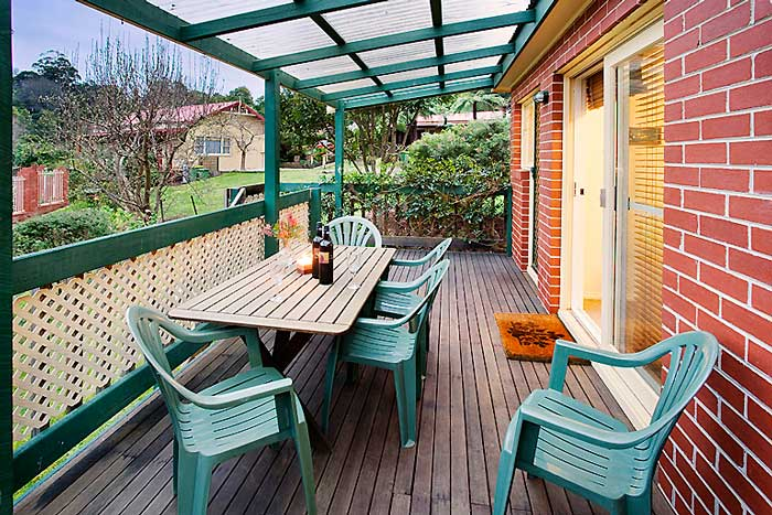 Covered verandah with ample seating and mountain views over the garden